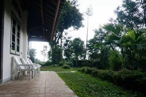 Pondok Buah Sinuan Bandung - Teras depan kamar dengan view pegunungan, taman, kolam ikan, dan kota Lembang